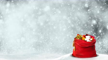 bolsa de hielo : Santa Present Bag Silver Glitter Swirl 4K Loop features a red Santa bag full of presents sitting in the snow with swirling clouds and silver glitter particles rising in the background Archivo de Video
