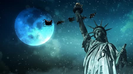 mutlu yeni yıl : Statue of Liberty with Santa in a Winter Snow 4K Loop features the Statue of Liberty with snow falling, clouds moving, and Santa flying across a full moon in the sky in a loop Stok Video