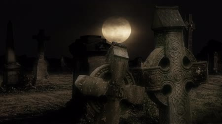 Old Cemetery Halloween moon 4K features an old cemetery with some Celtic crosses in the foreground and an orange moon rising in the background with a bit of halo effect on the whole composition. Perfect for Halloween.