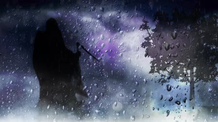 grim : Grim Reaper Silhouette Through Window features a silhouette of the grim reaper with cape flapping in the wind with mist and clouds moving and full moon in the background looking through a rainy window
