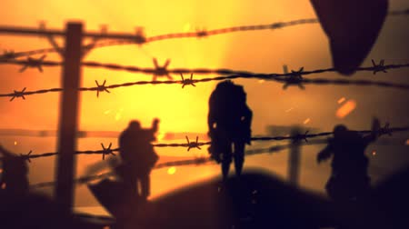 Barbwire Zombies at Sunset 4K Loop presenta siluetas de zombies caminando hacia adelante vistas a través de hebras de alambre de púas con nubes y partículas en movimiento. Archivo de Video
