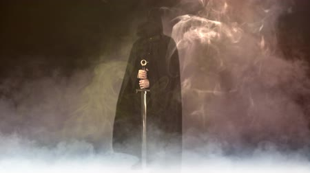 sírkő : Black Masked Figure with Sword in Smoke 4K features a figure in a black hooded cape holding a large broadsword in an environment of smoke, fog, and mist.