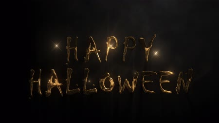 Happy Halloween Golden Glitter 4K Loop features a black atmosphere with smoke and golden glitter flowing upward forming the words Happy Halloween and the disappearing. Wideo