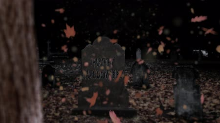 Happy Halloween Gravestone in Falling Leaves 4K Loop features the camera looking at a black sky and following leaves falling down until they land on the ground around a tombstone that says Happy Halloween.