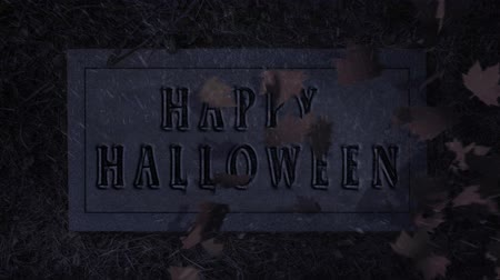 надгробная плита : Happy Halloween Tombstone Leaf Reveal 4K features a scene opening with leaves on the ground with rain and lightning with leaves blowing away to reveal a Tombstone with Happy Halloween engraved on it. Стоковые видеозаписи