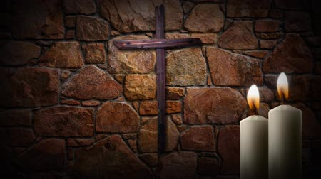 обещание : Candle Light Wooden Cross 4K Loop features a beautiful stone wall with an old wooden cross hanging and two white candles with moving flames in the foreground Стоковые видеозаписи