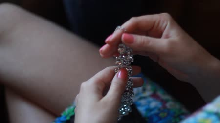 gyöngyszem : Bridal preparation, bride putting on jewelry, focus on bracelet