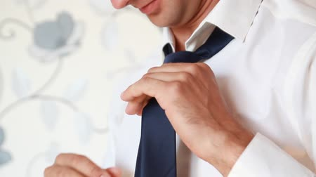 suit and tie : Man putting on tie clip, closeup, focused on clip