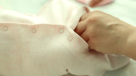 roupas : Moms Hands on Dress Clothes Baby Girl Stock Footage