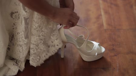 high heeled sandals : The bride wears white wedding shoes with her hands