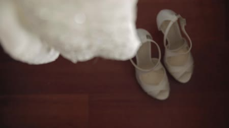 footgear : The bride wears white wedding shoes with her hands