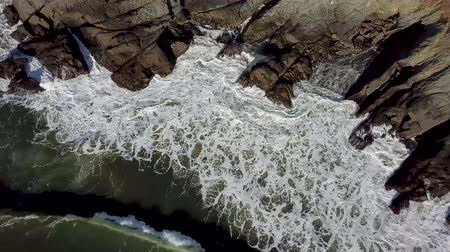 Aerial top view of sea waves hitting rocky shore