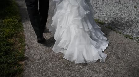 view of the legs, the bride and groom are walking, a beautiful train dress Stock mozgókép