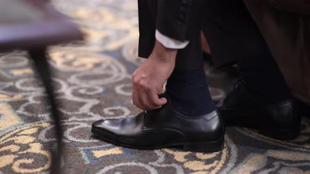 Wedding groom tie shoelaces on black shoes at home