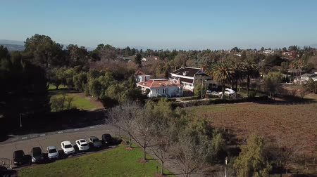 seçkinler : Aerial. beautiful big house in the middle of a field surrounded by palm trees Stok Video