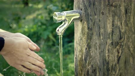 крупные планы : Hand washing at garden tap. Faucet with running water. Summer refreshment, rinsing with spring water. Sanitary close-up of footage, summertime day. Turning tap on. Dirty hands and chrome water spigot. Стоковые видеозаписи