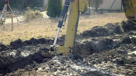 constructing : Big excavator is digging the foundations of the house. Excavating of hole. Construction machinery, ground works. Yellow digger works on building. Static day stabilized v-log shot. Bucket digs in clay.