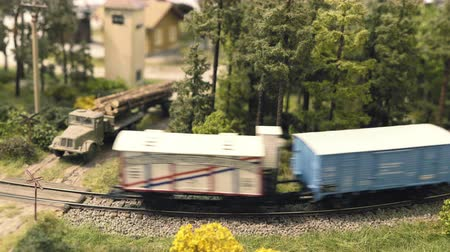Model railroad track. Miniature train runs through the curve. Trees and truck with wooden trunks on the body in background. Rail transport, entertainment toy industry