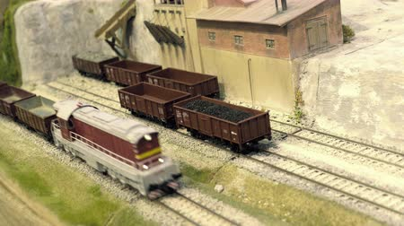Model railroad track. Cargo station in quarry. Miniature train runs through the curve. Rail transport, entertainment toy industry Stok Video