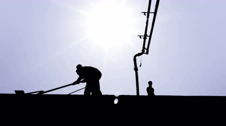 Workers are working on building ceiling, graphic silhouette stylization. Concrete casting pump to the roof of a family house. Concrete pump, sky and sun in background