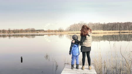 Mother and son standing on a small wooden pier at a beautiful pond and enjoying countryside. Red-haired woman and child are enjoying nice lake. Sunny day, family values, happy atmosphere Stok Video