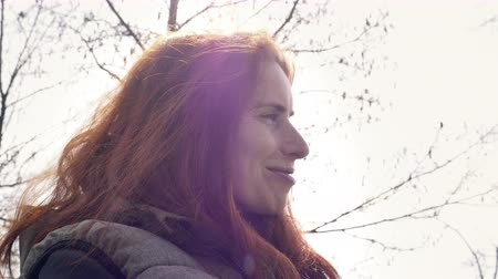 düzeltme : Close-up of red-haired woman on a white background. Talking woman with an ironic smile and backlight