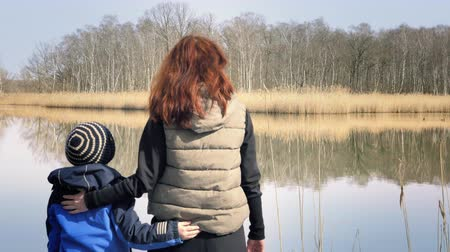 přirozeně : Woman and small boy standing on a small wooden pier at a beautiful pond and enjoying countryside. Red-haired mother and son are enjoying nice lake. Sunny day, family values, happy atmosphere Dostupné videozáznamy