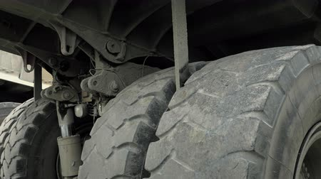 ivászat : Wheels and chassis of a huge truck. Lorry in quarry for stone and gravel extraction. Gravel processing plant, surface mine, total day shot Stock mozgókép