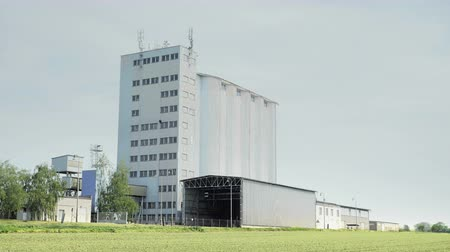 szűrés : Grain concrete silo building in flattened landscape, large seed lift. Footage of agriculture countryside, farming, farming in plain, flat land Stock mozgókép