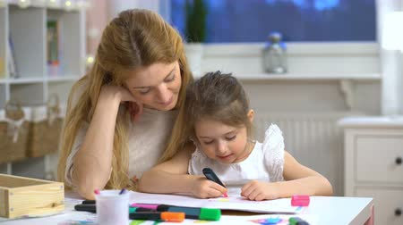 preschool : Little girl draws in the nursery. Mother looking how her child daughter drawing a picture
