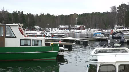 finlandês : Fishing boats, snow and lead-gray water of the Baltic Sea. Late fall on the coast of Scandinavia. Dolly shot.