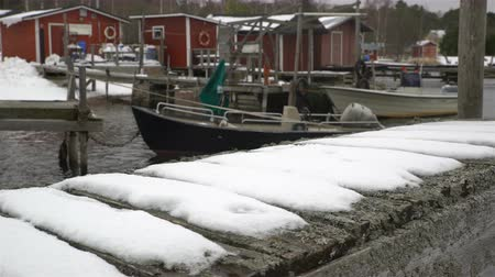 baltık : Old wooden jetty, fishing boats, snow and lead-gray water of Baltic Sea. Dolly shot