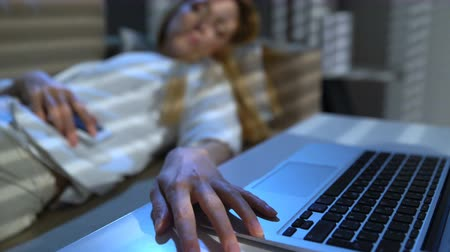 бухгалтер : Tired businesswoman sleeping on the couch in the office with laptop and phone. Close-up of her hand on the keyboard. Dolly shot