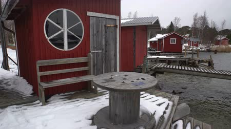 finlandês : A lot of small fish houses for fishing gear and boats on Baltic sea in winter. Old wooden jetty, fishing boats, snow and lead-gray water. Dolly shot Stock Footage