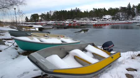 ryba : Fishing boats, snow and lead-gray water of the Baltic Sea. Late fall on the coast of Scandinavia. Dolly shot.