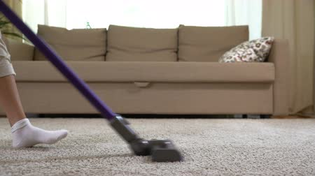 temizleme maddesi : A woman uses a vacuum cleaner to clean the carpet. Close up. Dolly shot Stok Video