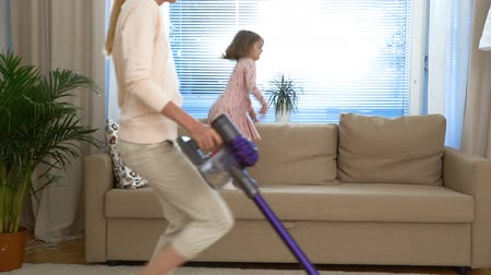 temizleme maddesi : Housewife dancing with a vacuum cleaner in the living room. Her little daughter jumping on the couch. Slow motion.