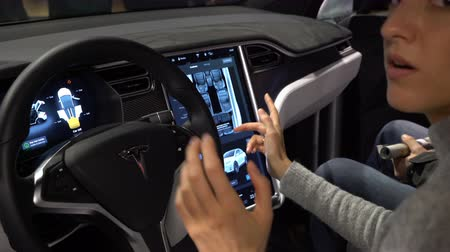 tesla car : HELSINKI, FINLAND - NOVEMBER 04, 2016: The interior of a Tesla Model X electric car with large touch screen dashboard. Woman tasting a new vehicle functions. DIGIEXPO 2016 in Messukeskus Expocenter.