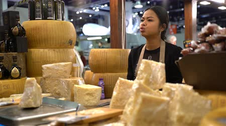 parmigiano : HELSINKI, FINLAND - OCTOBER 27, 2016: Seller of Italian products demonstrates the old lady collectors vinegar. Annual Food fair WINE AND FOOD 2016, expocenter Messukeskus.