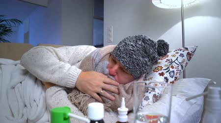 грипп : Sick Man Wearing A Warm Cap And Scarf In A Bed Coughs And Measures Temperature. Стоковые видеозаписи