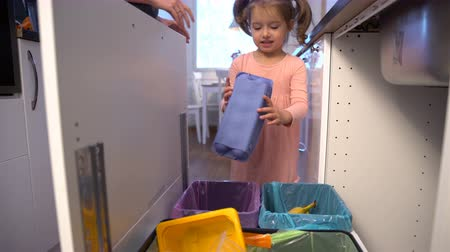 reutilização : Little Girl Drops The Trash Into Kitchen Recycling Bins.