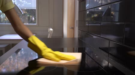 dezenfektan : Housewife wipes the surface of the electric stove with a special cleaning cloth. Dolly shot. Stok Video