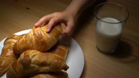 kruvasan : Fresh croissants and milk on wooden table. Childrens hand takes the croissant from the plate. Stok Video