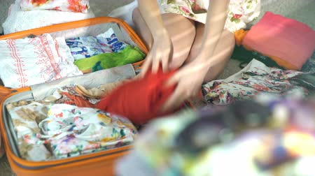 bagagem : woman is carefully packing a luggage for a new journey
