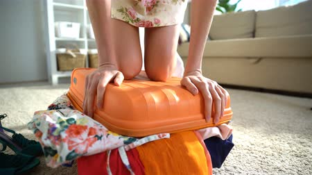 chock : A young woman is trying to close the chock-full orange suitcase.