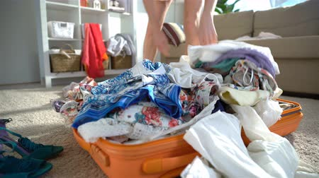 chock : A young woman is haphazardly packing and trying to close the chock-full suitcase. Close up. Time lapse.
