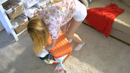 chock : A young woman is trying to close the chock-full orange suitcase. Top view.