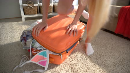 chock : A young woman is trying to close the chock-full suitcase.