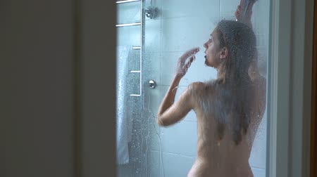 nu : Young slim woman taking a shower and washing her hair. Dolly Shot. Slow Motion.