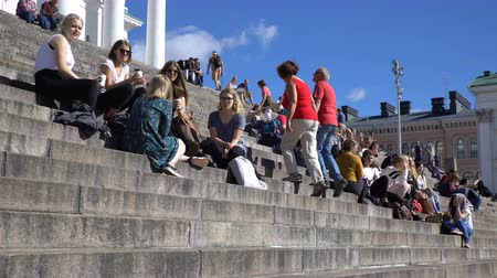 senate square : HELSINKI, FINLAND - AUGUST 31, 2016: Many young people, students and tourists sit on the steps in front of the Cathedral on the Senate Square in Helsinki.